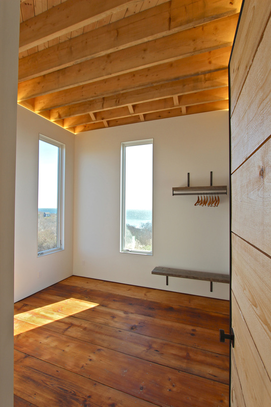 QUARTER design studio + EngineHouse | Seaside Residence | Block Island, RI – master bedroom with exposed ceiling rafters, LED cove lighting, and reclaimed wide-plank flooring (photo provided by EngineHouse)
